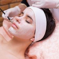 Girl receiving facial mask treatment in beauty spa.